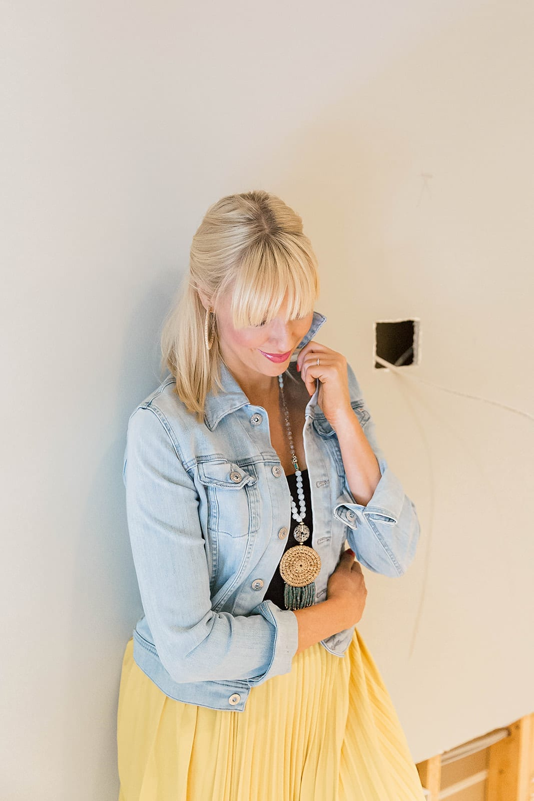 AG Jean Jacket with bright yellow skirt and blue long layered statement Anthropologie necklace. Fringe bangs hairstyle.