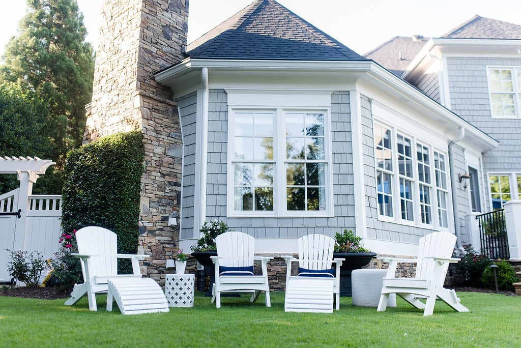 Adirondack Chairs on Sale with gray cedar siding house and blue sunbrella pillows.