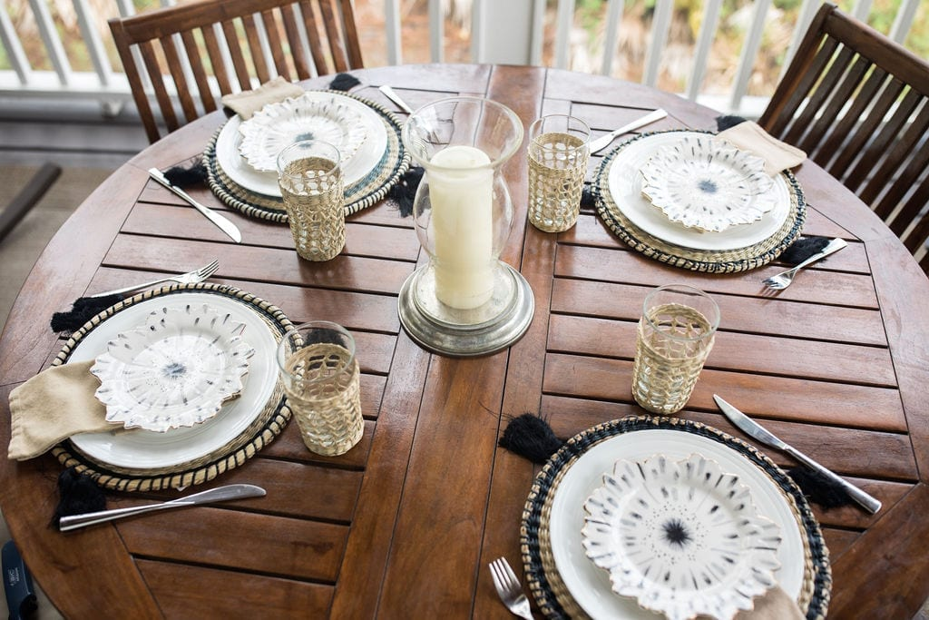 Gold and black table settings are both coastal and glamorous all t once with hints of gold leaf, wicker rattan round placemats and wicker cups. Add glamorous Anthropologie plates for an elegant table.