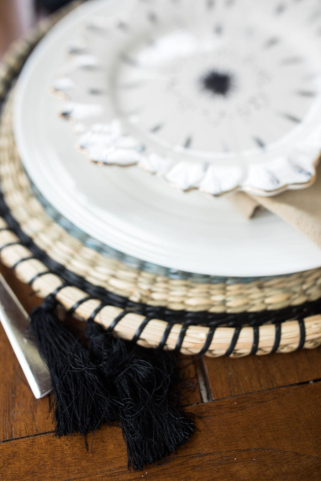 Anthropologie charger plates. Chargers with black tassels on round rotten placemat.