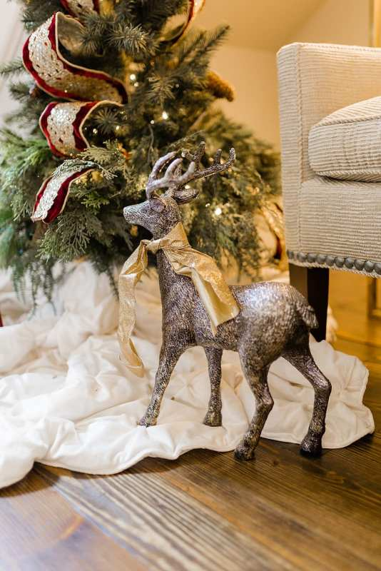 Gold Reindeer with miniature Christmas tree for foyer Christmas decor ideas.