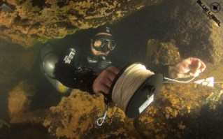 A cave diver makes a tie of using a reel. This will secure his continuous guideline to exit the cave