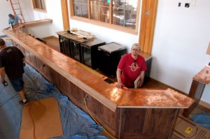 By Tommy Stafford : Brewmaster, Jason Oliver, stands behind the newly installed copper topped bar at Devil's Backbone near Wintergreen.