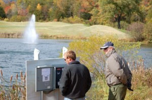 David Hall, right, watches as the final connections are made and the fountain is turned on.
