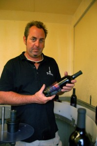 ©2009 NCL Magazine : Jeff Stone,co-owner of Wintergreen Winery holding one of his winning red wines from a past bottling.