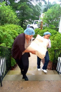Volunteers carry large bags of grain into Grace Episcopal Wednesday afternoon.