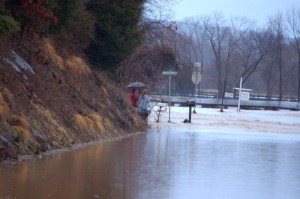 ©2010 www.nelsoncountylife.com : Photos By Tommy Stafford : Two people look at a raging Rockfish River that has blocked Route 635 (Greenfield Rd) at the intersection of Cole's Farm Road. Click any photo to enlarge.