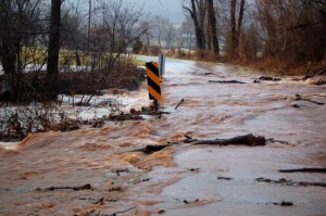 ©2010 www.nelsoncountylife.com : Water spills over the Spruce Creek bridge on Glenthorne Loop Monday morning. Most roads in Nelson have reopened to traffic since then.