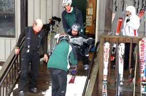 Sam Shaver, Casper Cosmo, and Damion Armour assist Michael Murphy down the steps and onto the snow.