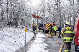 Crews with WFD extend a bucket from a fire truck to help batle the Sunday afternoon blaze on Devils Knob at Wintergreen.