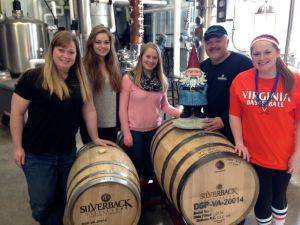Photo Courtesy of Christine Riggleman : A celebrity of sorts made a stop in Afton at Silverback Distillery on Saturday afternoon. The Travelocity Gnome hopped atop one of the aging barrels there to meet and greet with the entire gang at Silberback.