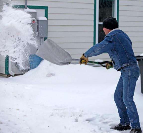 Mark Warren shovels snow on South Locust Street Friday