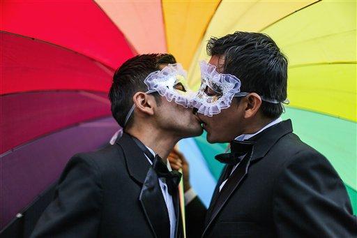Men kiss under a rainbow umbrella during a gay pride parade  (AP Photo/Sebastian Castaneda)