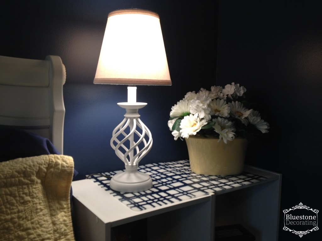 A white lampshade in this navy bedroom was the best choice for bedside reading.