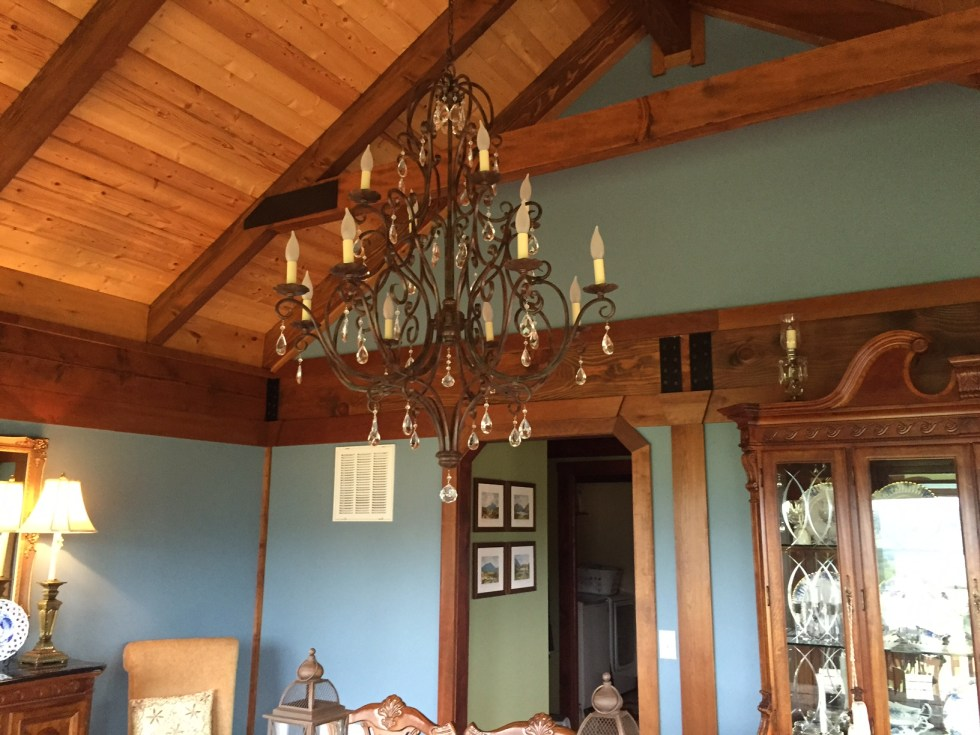"""AFTER: I chose Benjamin Moore's """"Wild Blue Yonder"""" for the paint color in this dining room. Now the chandelier is noticeable against the log ceiling beams."""