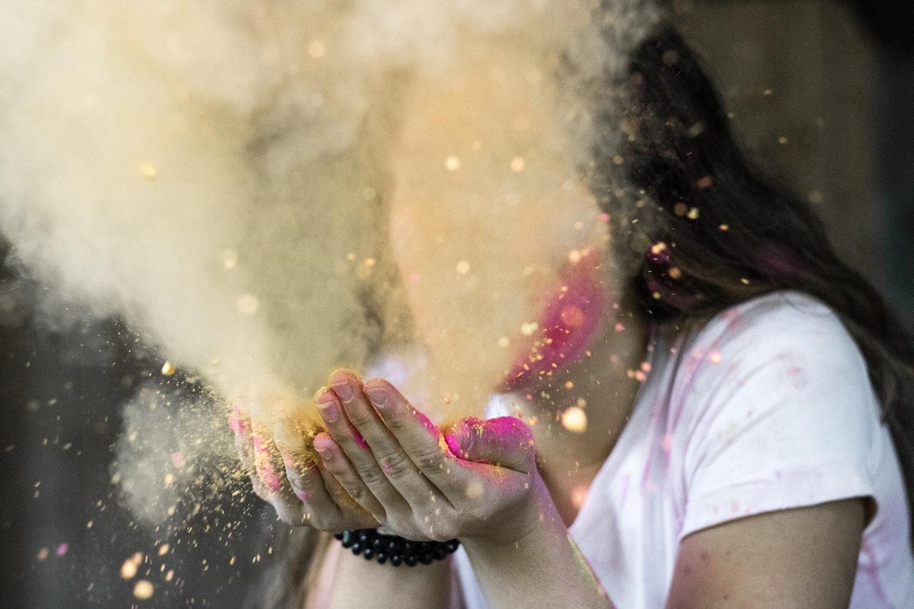 a girl blowing glittery dust