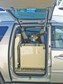 Articulating Chair Lift Fully Stowed Behind Gullwing Door in Cadillac Escalade