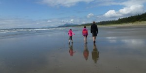 Two girls and a father walking down an empty beach with their reflections in the wet sand