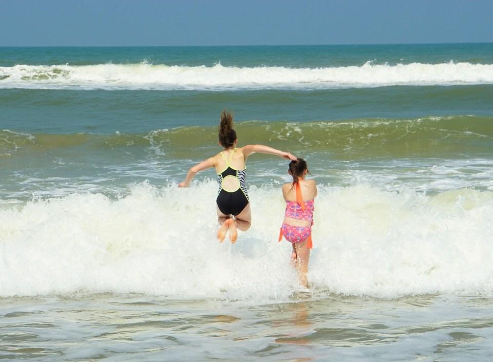Girls play in the waves on Cua Dai Beach