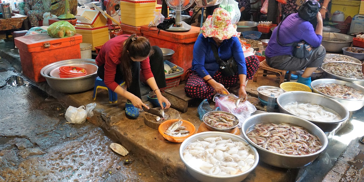 Women prepare fish and shrimp in the Kampot Market