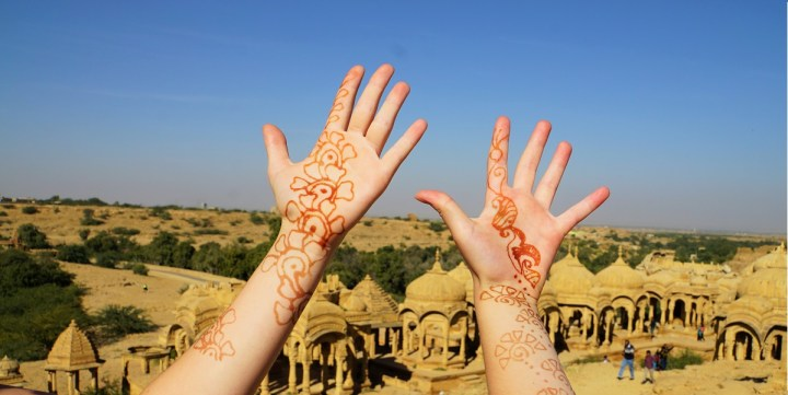 The girls raise their henna hands in front of the royal tombs at Bada Bagh