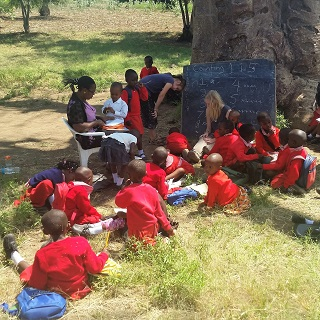 One Kindergarten class is held outside under a baobab tree