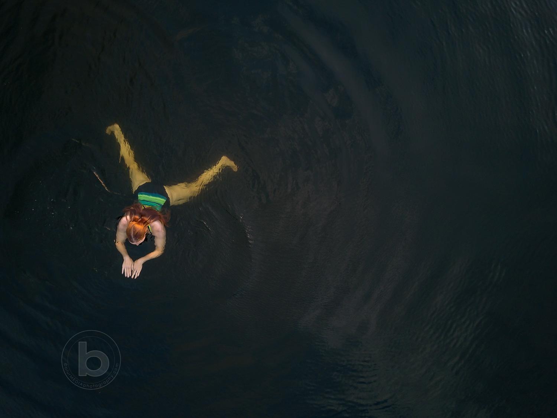 Aerial photo of a woman (40) swimming in a lake in the Kawartha cottage region near Haliburton, Ontario, Canada