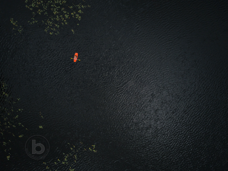 Aerial photo of a lake in the Kawartha cottage region near Haliburton, Ontario, Canada with boy paddling a small kayak alone.