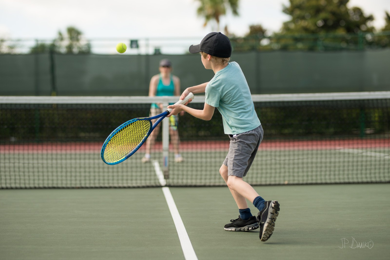 Mother and son physically fit play tennis together on summer Florida vacation