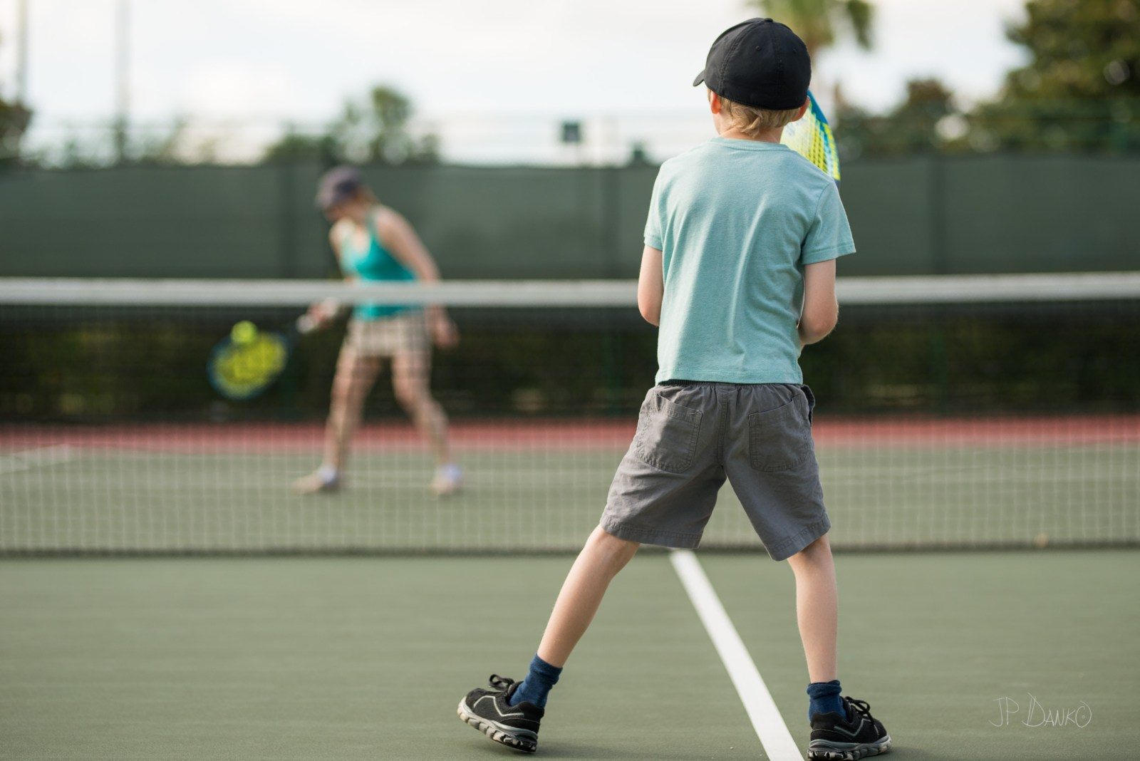 Mom in tank top returns ball to son playing tennis on summer Florida vacation
