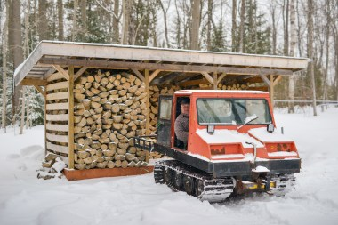 Rare antique snow groomer in Muskoka woods snow field by wood shed