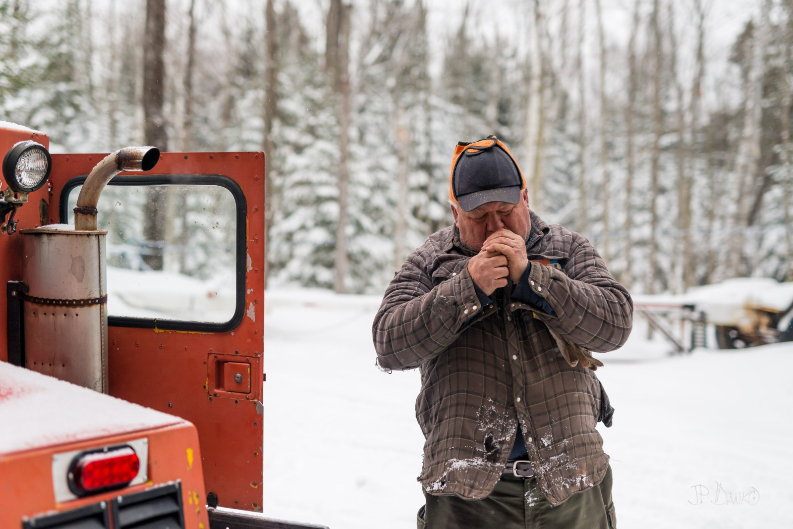 Rustic northern Ontario man leaves cab of snow grooming machine to light a cigarette