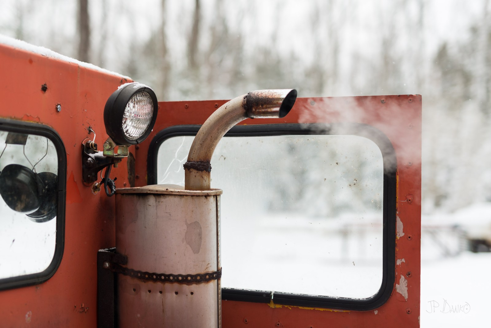 Exhaust spews from rusty old muffler strapped to cab of orange vintage snow groomer