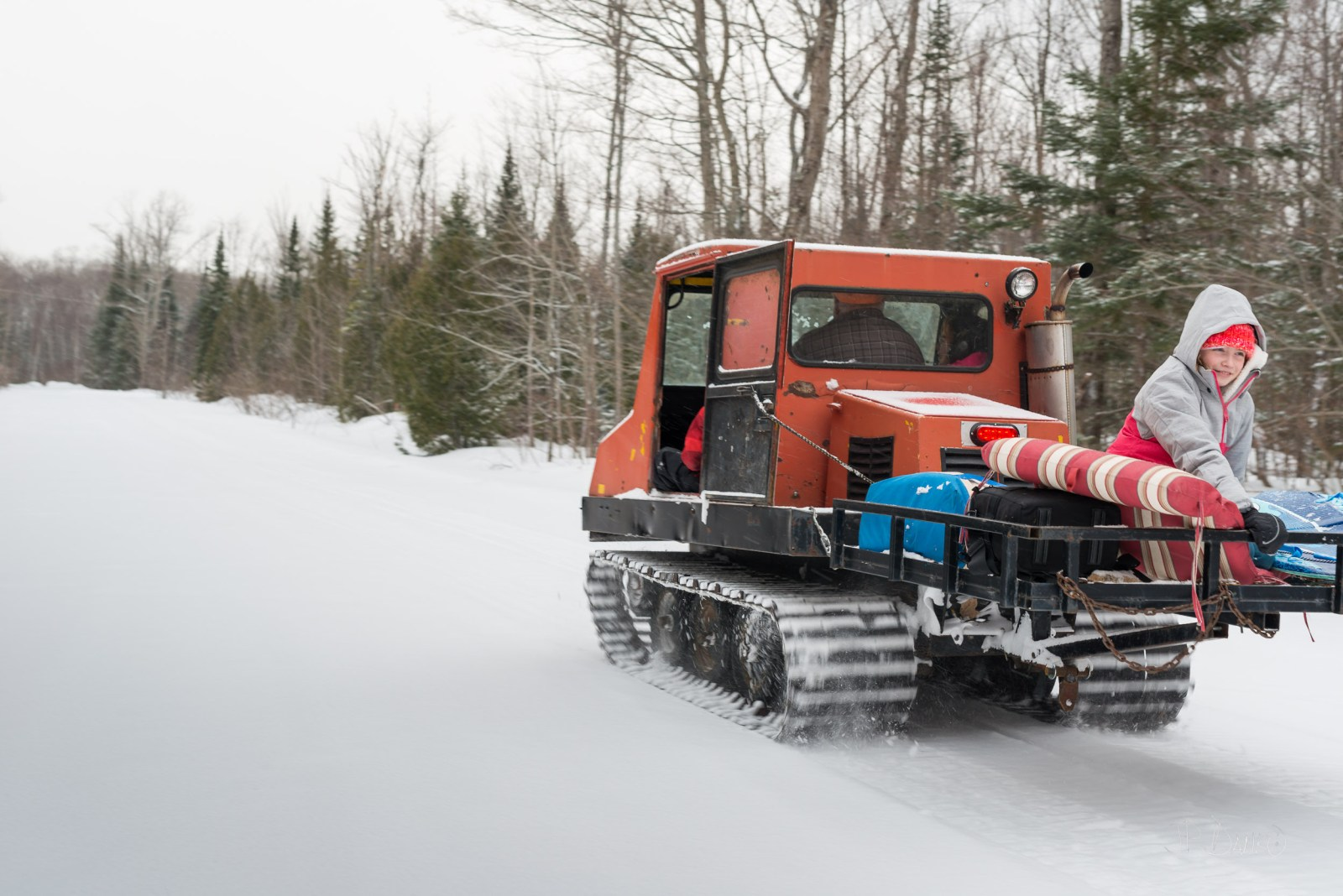 Girl in winter jacket sits in the bed of antique snow groomer moving through Muskoka forest