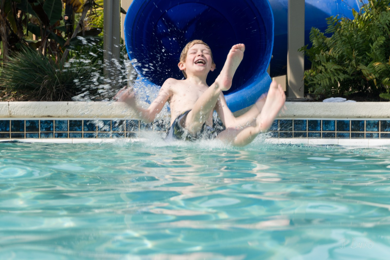Boy laughs on water slide into cool blue holiday swimming pool