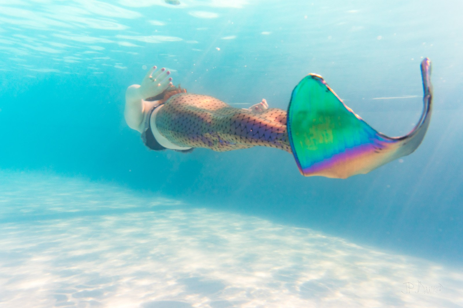 Underwater view of woman on holiday swimming in pool with colorful iridescent mermaid tail