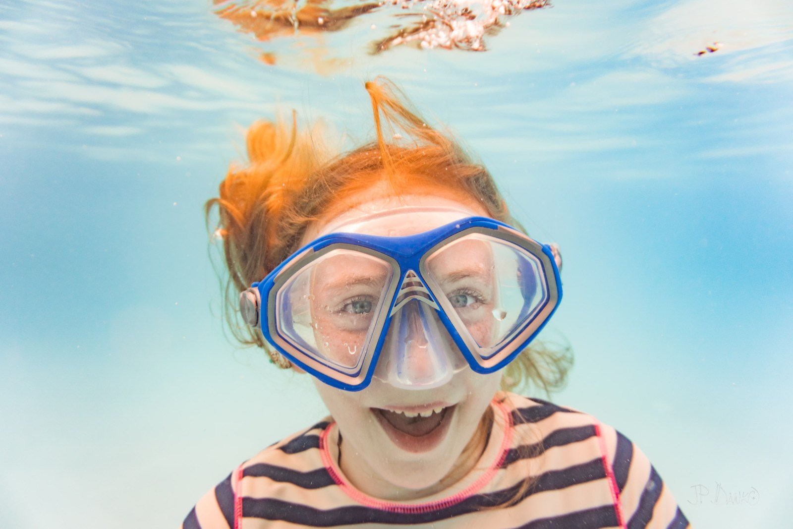 Underwater view of girl on holiday swimming in pool laughing in goggles