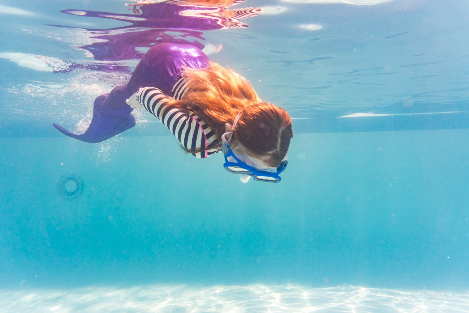 Underwater view of girl on holiday swimming in cool blue pool with colorful mermaid tail