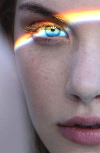 Woman with rainbow light over her eye