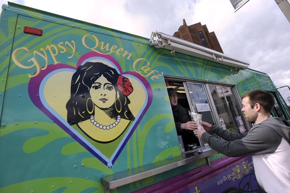 Gypsy Queen Café's J.A. Peters, left, hands a Gypsy Crab Cone to Matt Groncki