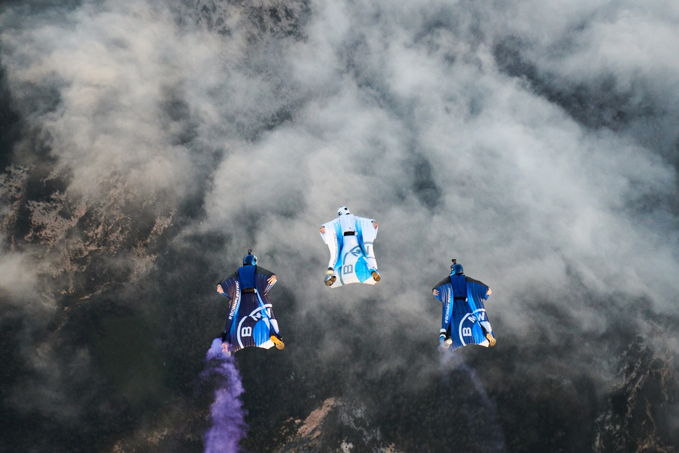 Three people flying with BMW Wingsuits.
