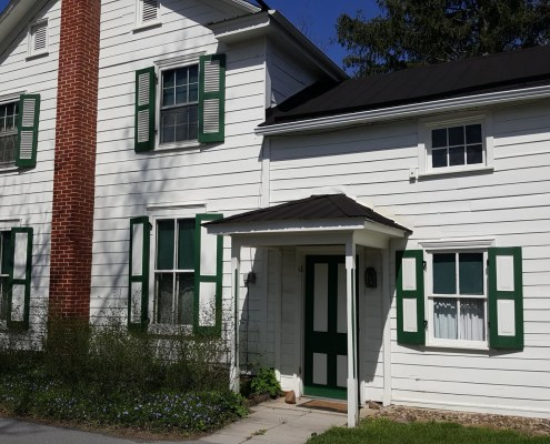 2 story building with white siding and green window shutters