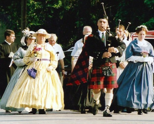 Women in hoop skirt dresses and a man in a kilt playing bagpipes