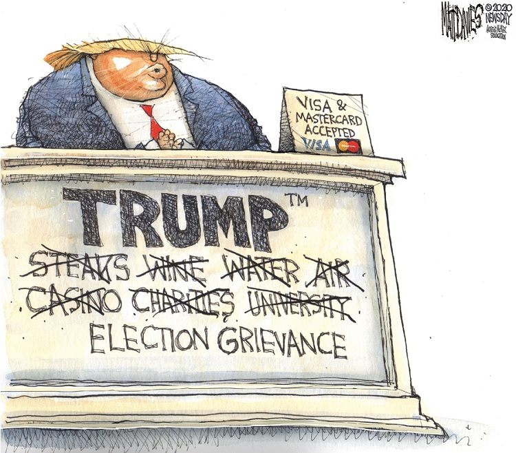 Donald Trump behind desk next to sign reading,