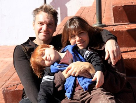Family relaxes in the sun on the temple steps.