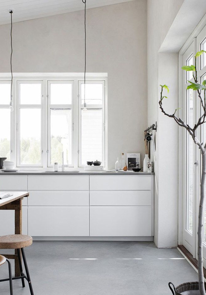 4 cuisines blanches avec un sol en béton