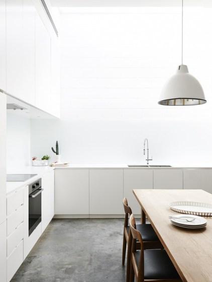 4 belles cuisine blanches avec un sol en béton