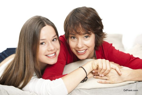 Smiling teenage girl and her mother lying on the bed