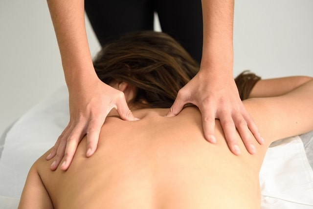young woman receiving a back massage in a spa cent GJUAXSW scaled min