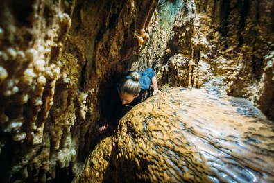 Squeezing through the small crevices of Cango Caves on the Adventure Tour